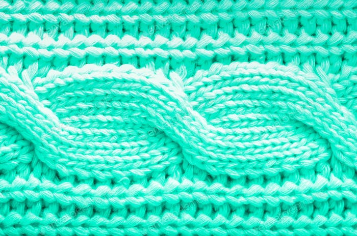 Knitted texture. Pattern fabric made of wool in mint color. Background, copy space. Trendy green and