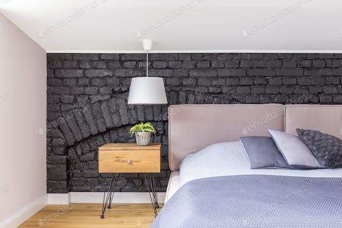 Bett gegen schwarze Ziegelmauer