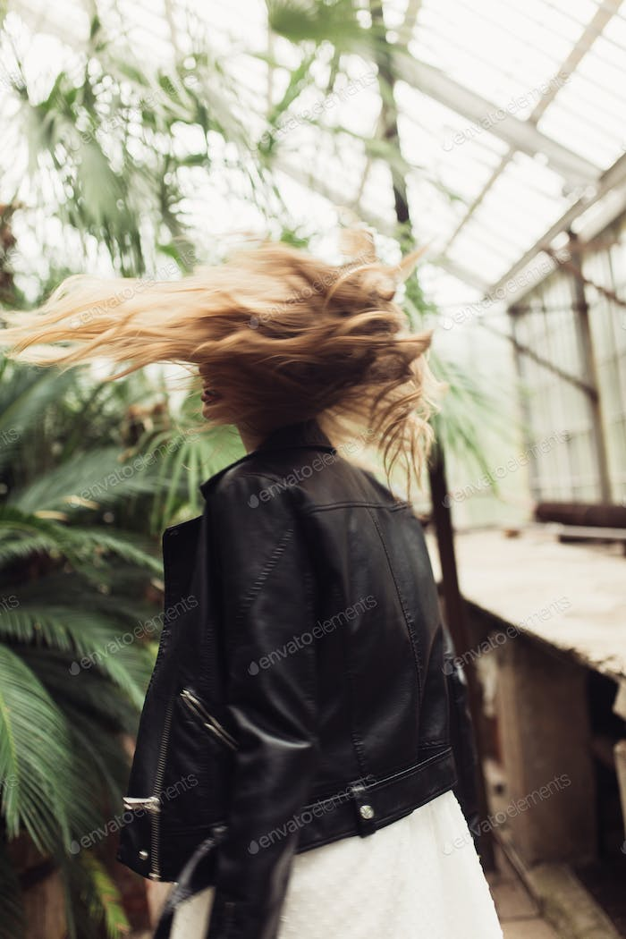 Young beautiful woman from back in black leather jacket and whit