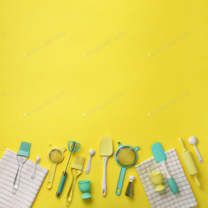 Turquoise cooking utensils on yellow background. Food ingredients. Cooking cakes and baking bread