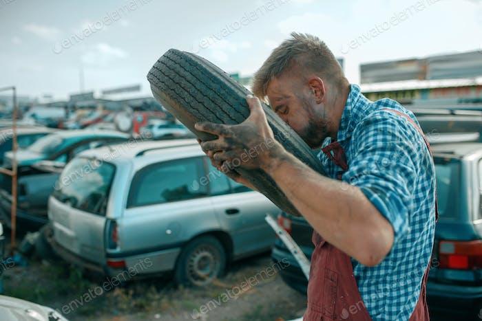 Reparaturmann pumpt den Reifen auf Auto Schrottplatz