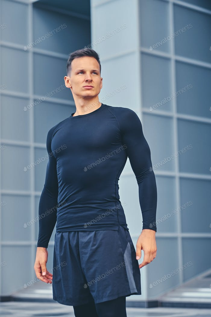 A man in a black sportswear over modern building background.