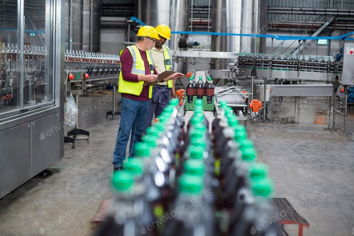 Zwei Fabrikarbeiter überwachen Kaltgetränkeflaschen auf der Produktionslinie