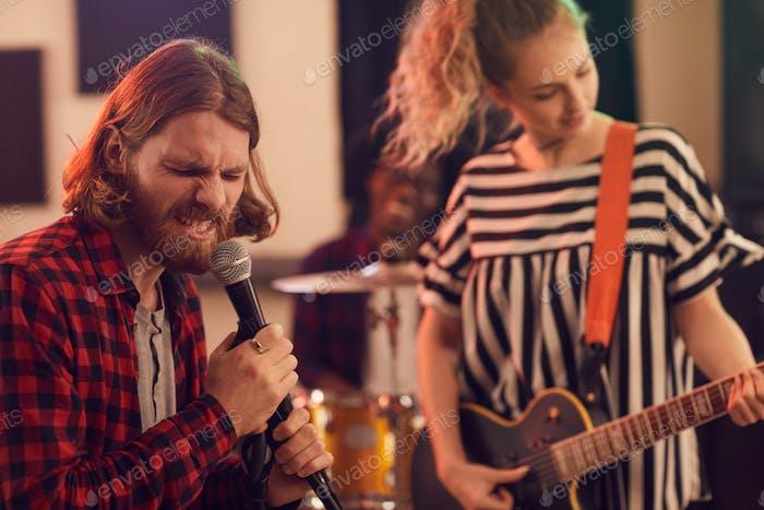 Bärtiger junger Mann singt zu Mikrofon mit Rockband