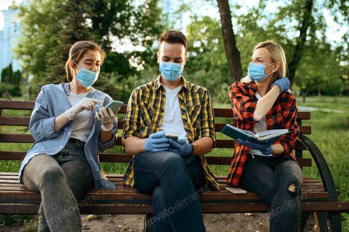 Young people in masks sitting on bench, quarantine