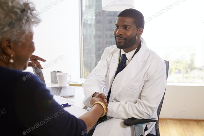 Senior Woman Shaking Hands With Male Doctor Cosmetic Surgeon In Office