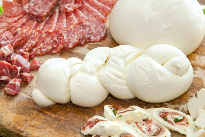 Mozzarella on cutting board with salami and cheese.