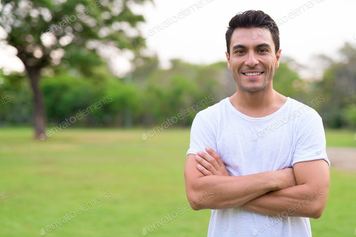 Happy young Hispanic man smiling with arms crossed in the park outdoors