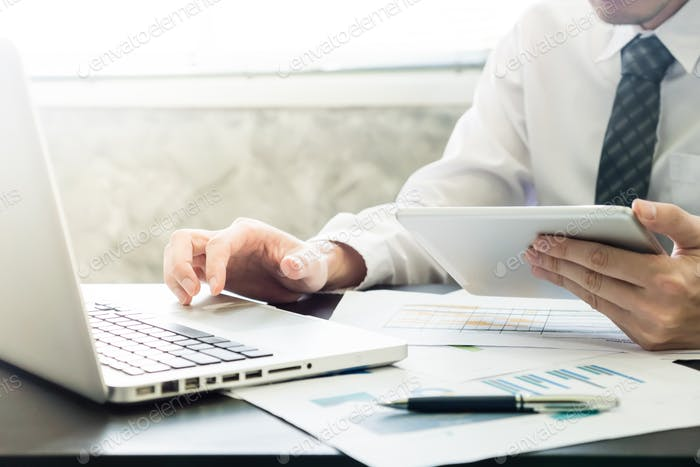 Businessman using tablet and laptop on the desk.