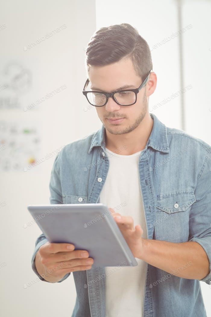 Serious man using digital tablet at office
