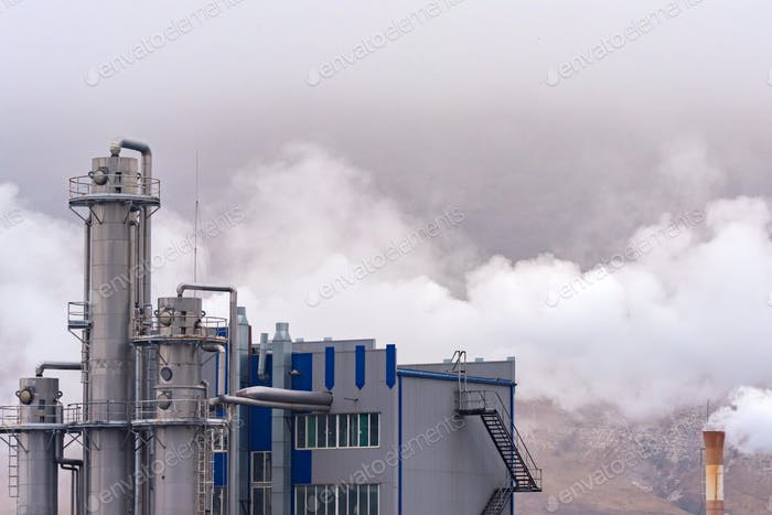 Luftverschmutzung durch Fabrikrauch. Graue Fabrik gegen bewölkten Himmel