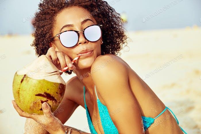 Молодая женщина расслабляющий на пляже пить из кокоса