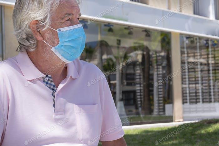 Hombre mayor con máscara médica debido al coronavirus delante de las tiendas cerradas por encierro.