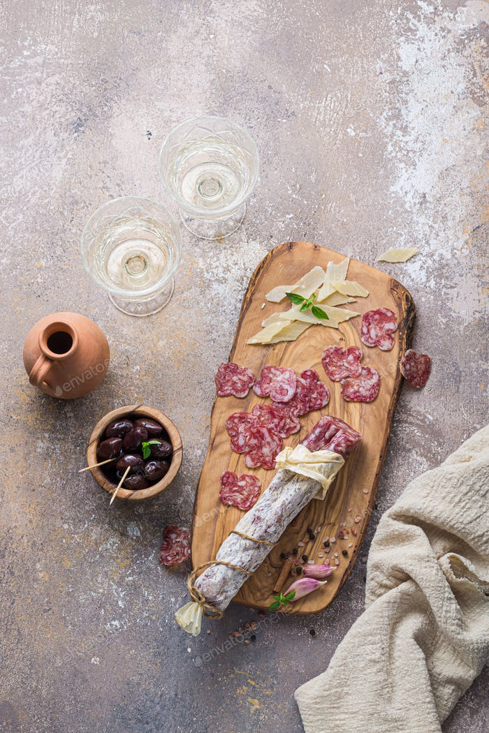 Italian salami on wooden board with cheese and olives