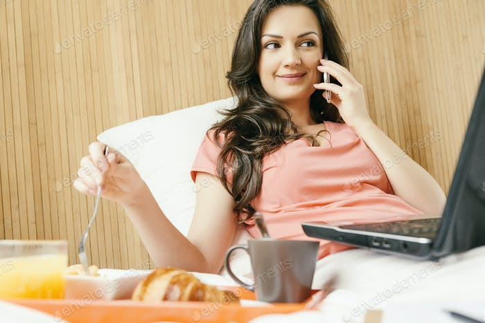 Woman using her mobile phone and having breakfast