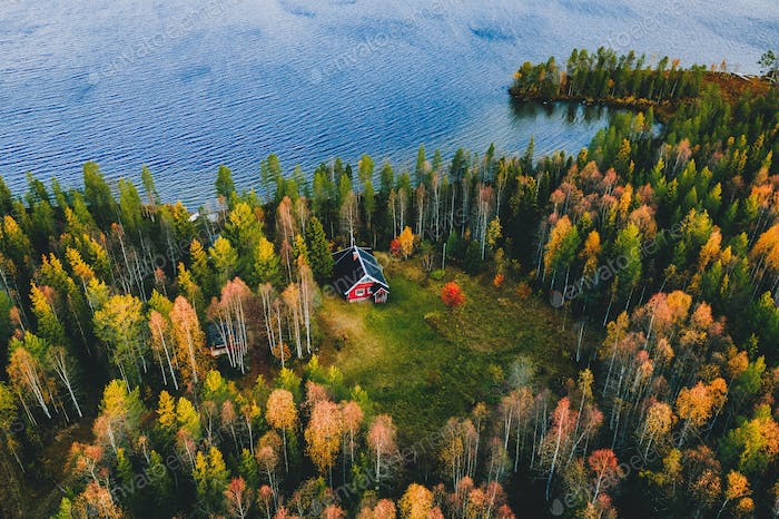 Aerial view of log cabin in autumn colors forest by blue lake in rural fall