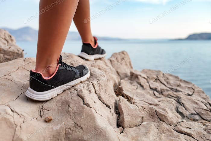 Close up legs of hiker young woman on trekking trail along sea bay