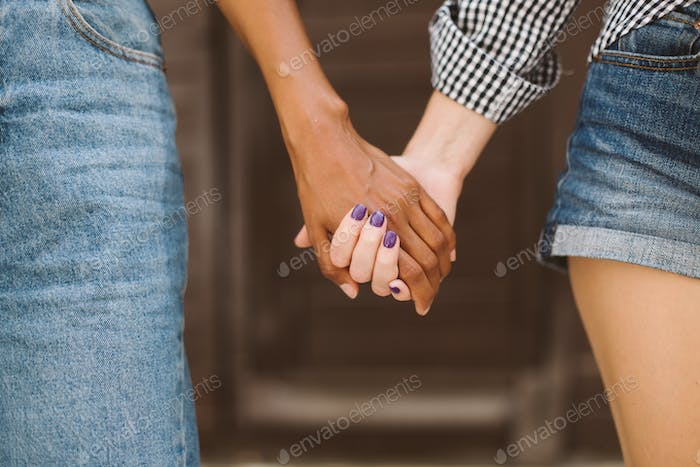 Close up african american and caucasian women holding each other