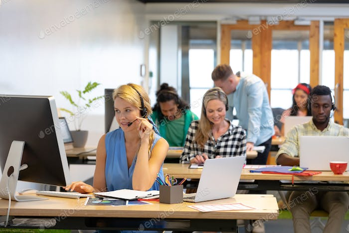 Front view of diverse customer service executives working at desk in a modern office