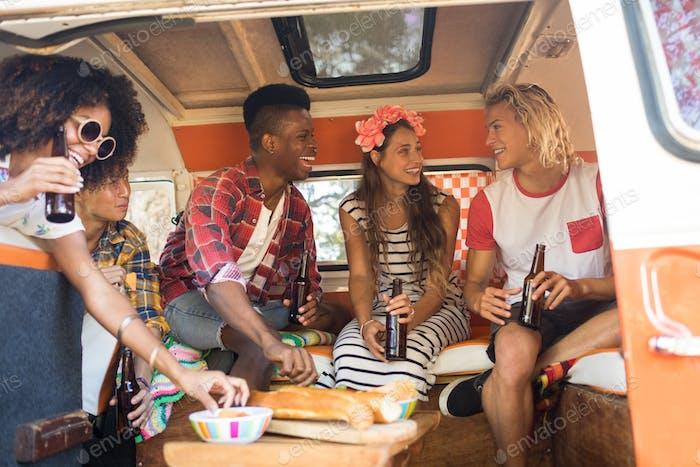 Happy friends holding beer bottles in camper van