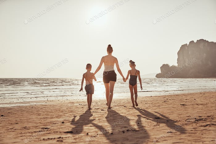 Mother and children walking together on a beach holding hands