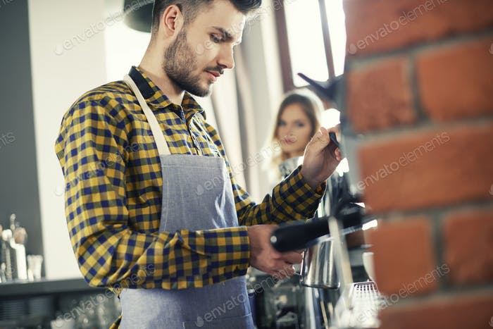 Waiter concentrating while making coffee