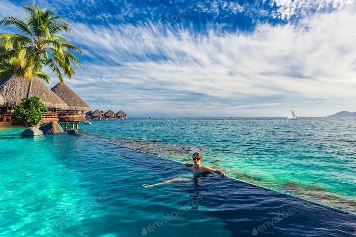 Woman in the infinity pool in exotic island resort with bunalows