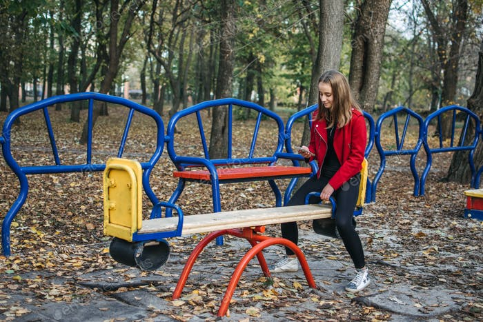 Gen z, generation z, Zoomers device addiction, digital detox. Teenager girl alone rides on a swing