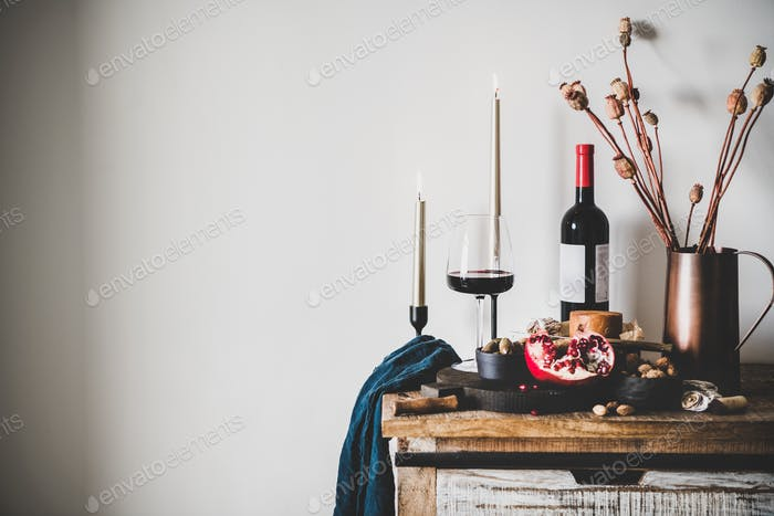 Red wine and snack set over kitchen counter, copy space