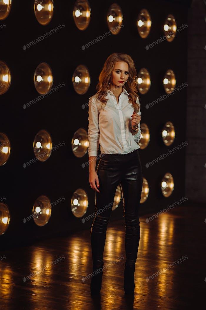 Business Woman in einem weißen Hemd vor dem Hintergrund von brennenden Lampen im Inneren eines dunklen