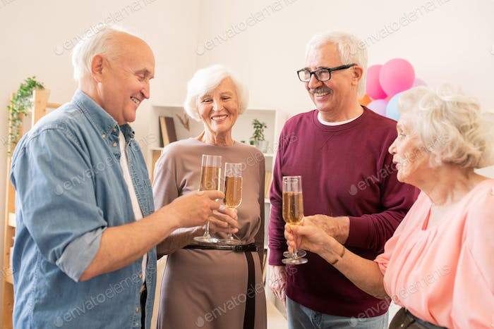 Booze party of four senior friends with champagne
