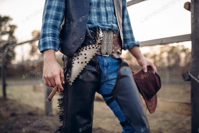 Cowboy in Lederkleidung Posen mit Zigarre