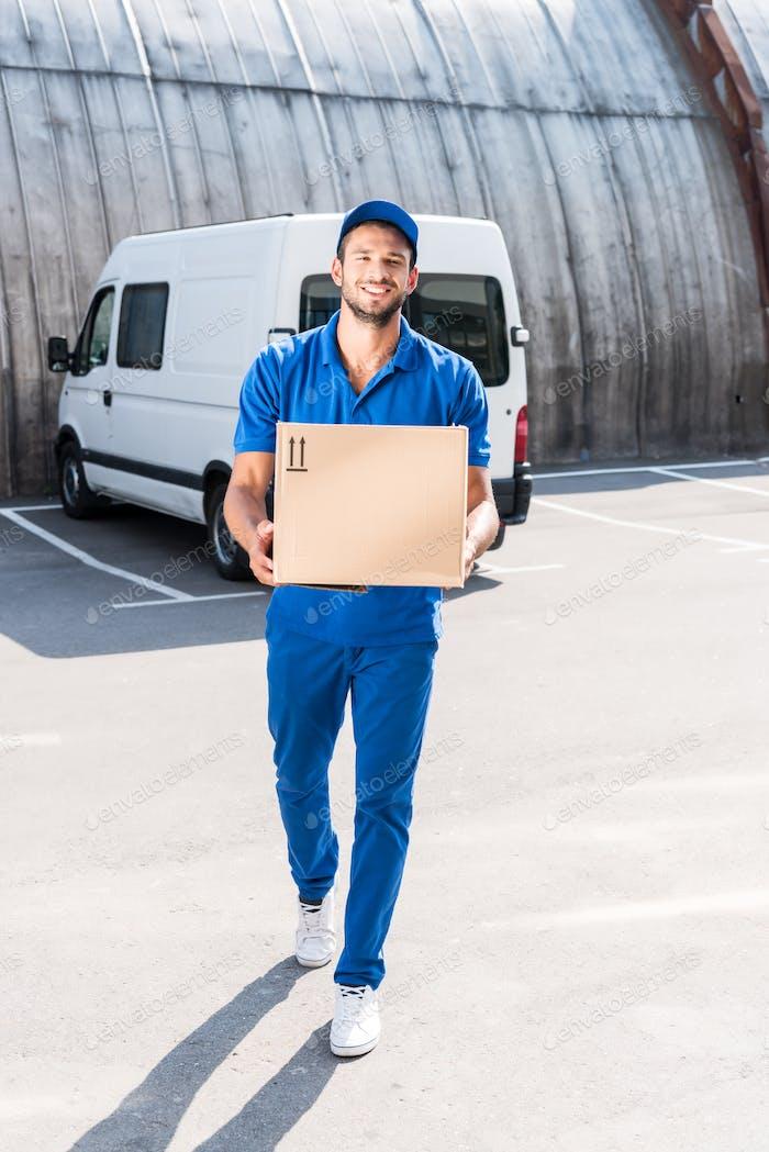 lächelnd Lieferung Mann mit Kartonschachtel