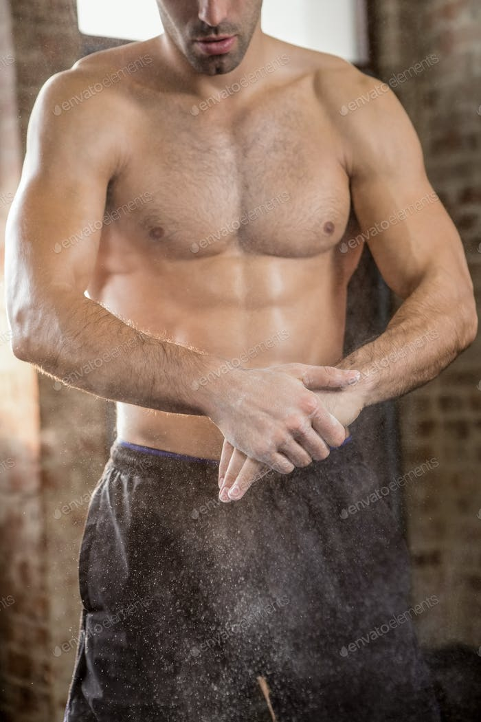 Midsection of man applying chalk powder at the gym
