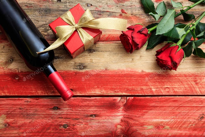 Valentines day. Red wine bottle, roses and a gift on wooden background