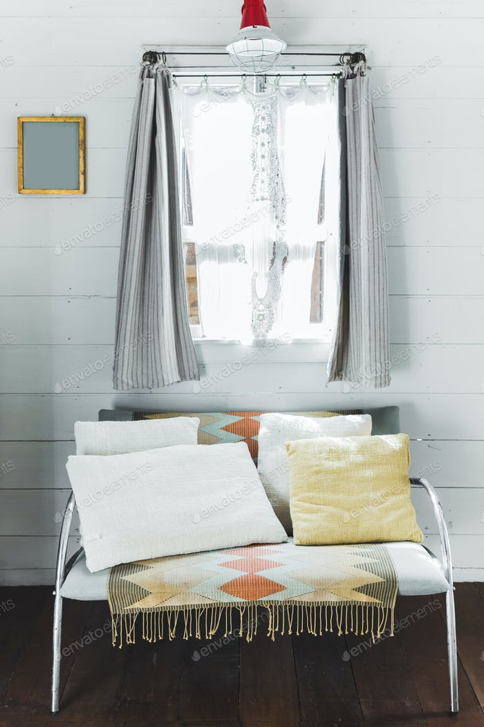 Sofa with white and beige pillows in front of window with vintage shutters. Interior