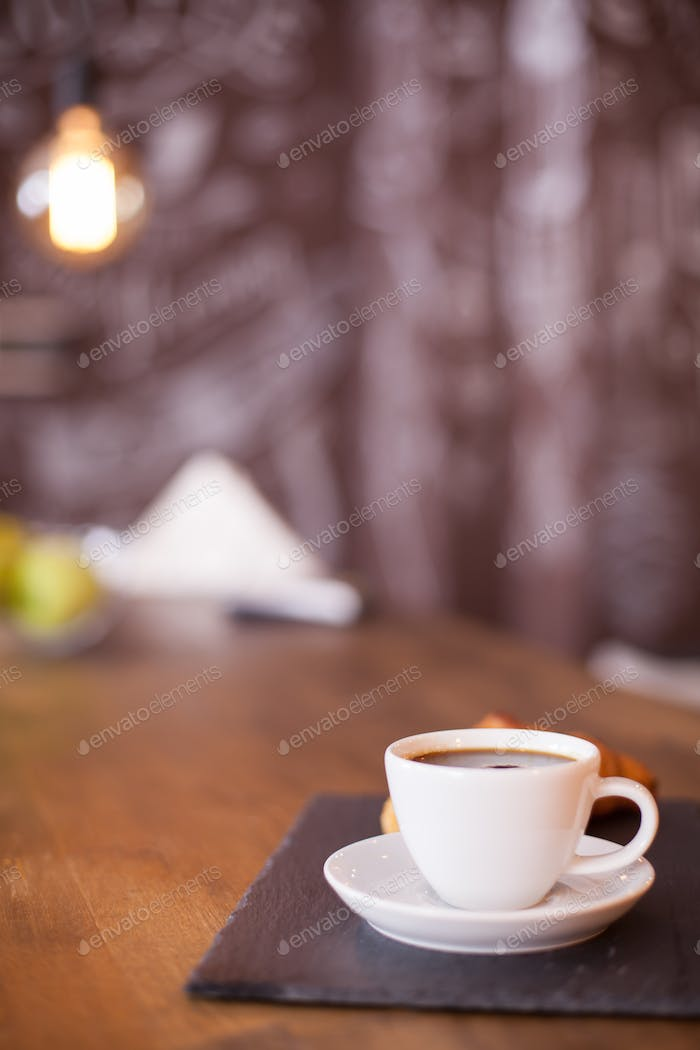 Minimalist composition of a cup of coffee on a black stone plate with blurred background
