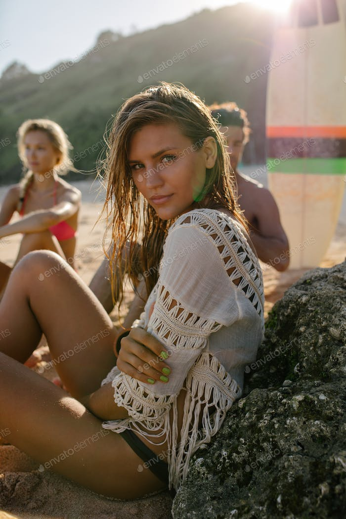 Young woman sitting on the beach with her friends