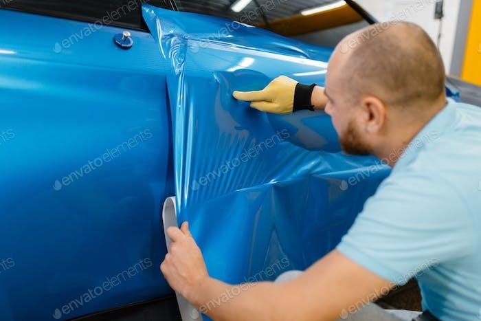 Car wrapper installs protective vinyl foil or film