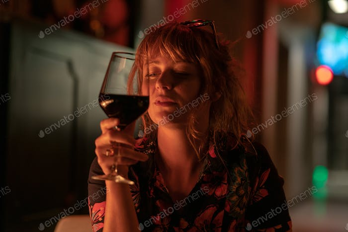 Beautiful ginger girl drinking a glass of red wine near a fire p