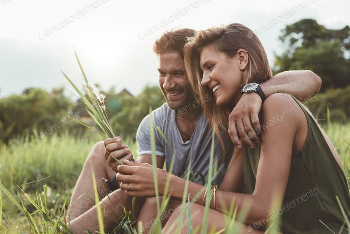 Smiling young couple sitting together outdoor
