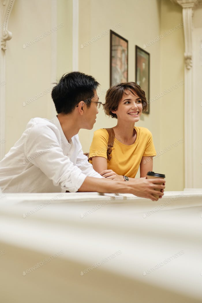 Two young attractive smiling international student friends happily talking at corridor of university