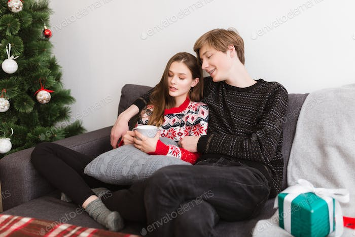 Young beautiful couple sitting on sofa at home and spending time together at Christmas time