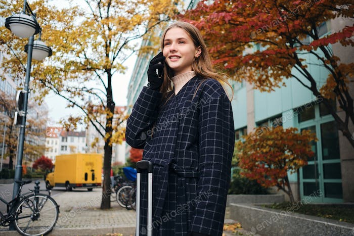 Beautiful stylish girl happily talking on cellphone while standing on city street with suitcase