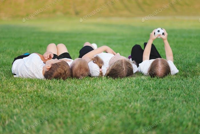 glückliche Kinder liegen auf Fußballplatz