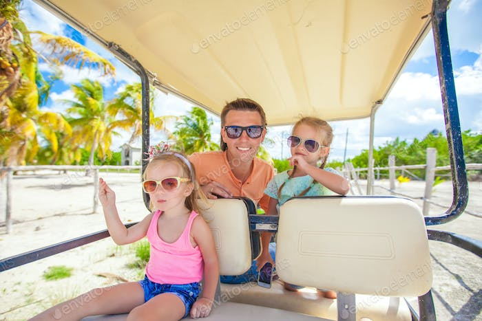 Dad and his little girls driving golf cart on tropical beach