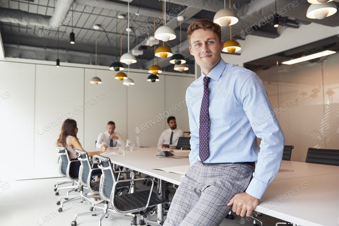 Портрет бизнесмена, стоящего в современном зале заседаний с коллегами