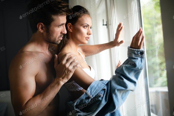 Schöne Frau und gut aussehende muskulöse Mann nahe beieinander in erotischer Pose