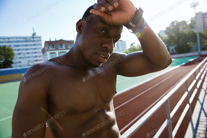 Close up of a young exhausted african athlete man resting