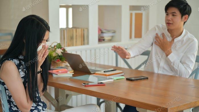 Una mujer joven estornudando mientras trabaja con un compañero masculino. Estaba aterrorizado por Covid-19.
